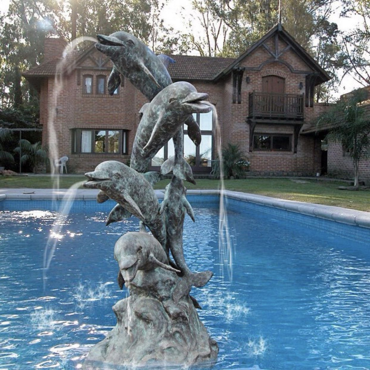dolphin fountain is sculpted in the pool