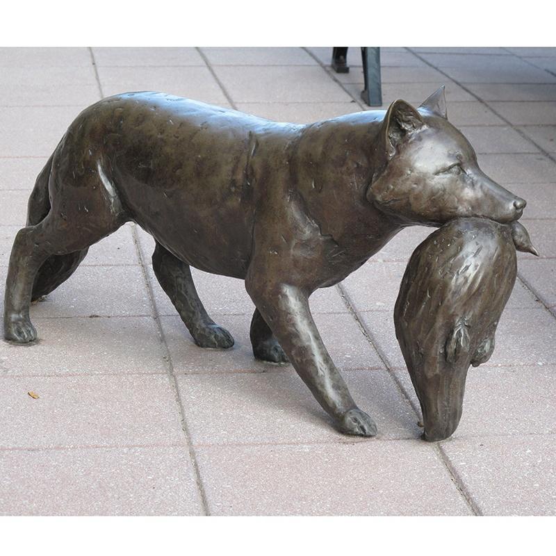 wolf carrying bird sculpture